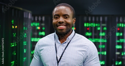 Fényképezés Close up of male young African American professional in server room with green lights on background
