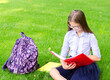 Leinwandbild Motiv Back to school. Education concept. Cute smiling schoolgirl in glasses sitting on grass with books and backpack