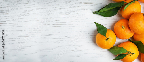 Fototapeta Fresh ripe tangerines with leaves and space for text on white wooden table, top view. Banner design obraz