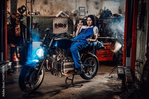 Obraz na plátně Hot brunette female mechanic in blue overalls relaxing smoking a cigarette while