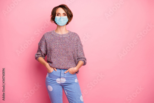 Portrait of her she nice pretty content healthy girl wearing safety gauze mask holding hands in pockets flue sickness illness disease preventive measures isolated over pink pastel color background