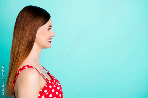 Closeup profile photo of attractive pretty lady bright pomade look side empty space smiling beaming toothy wear red dotted retro dress singlet isolated vivid teal color background