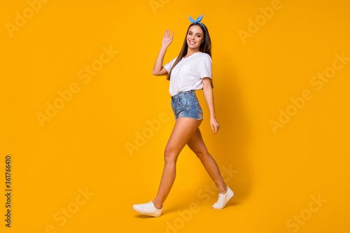Full size photo of charming candid lovely sweet girl go walk rest relax see look her fellow hold hand greet wear legs white jeans t-shirt footwear isolated bright color background