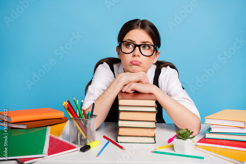 Photo of frustrated college girl sit table put hands head pile stack textbook look copyspace wear white black blouse overall uniform isolated over blue color background