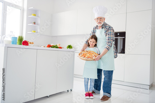 Full length body size view of cheerful grey-haired grandparent grandchild holding in hands tray baked domestic vegetarian pizza mushroom workshop help support in light white interior kitchen house