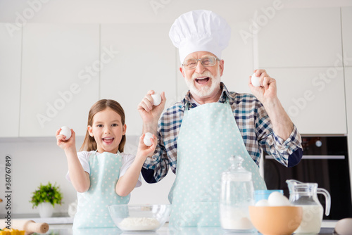 Photo of little girl granddaughter aged funny grandpa baking cookies together prepared ingredients hold eggs make dough bonding harmony best friends home kitchen indoors
