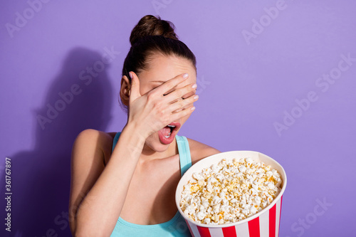 Portrait of horrified girl hold big pop corn box watch horror series afraid close cover hand face wear tank-top isolated over violet color background