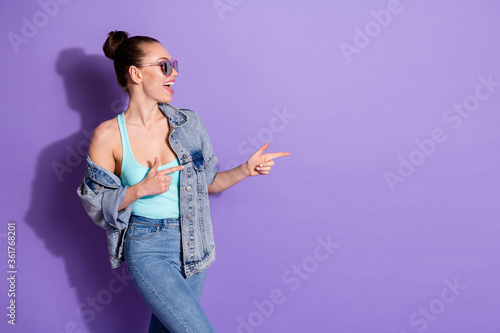 Profile side photo of positive cheerful girl promoter point index finger copyspace demonstrate incredible ads promotion wear tank-top isolated over violet color background
