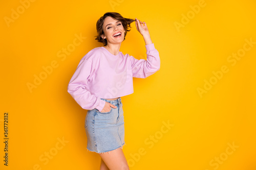 Obraz Portrait of her she nice attractive lovely pretty cute charming cheerful cheery girl playing with curl isolated on bright vivid shine vibrant yellow color background - fototapety do salonu