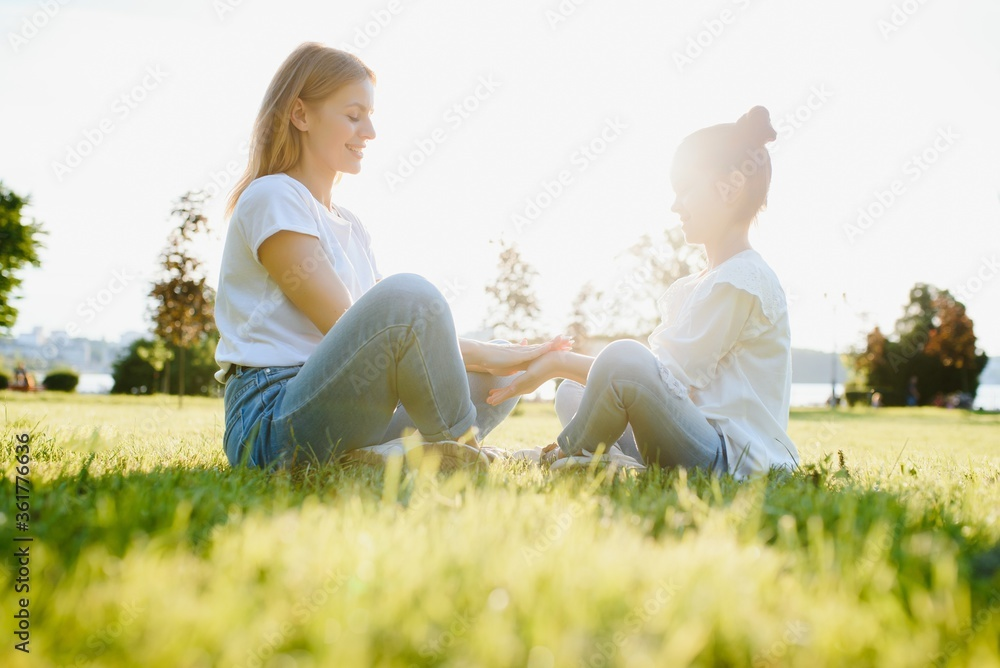 Fototapeta Happy mother and daughter relaxing in the park. Beauty nature scene with family outdoor lifestyle at spring or summer time. Happy stylish family resting together, having fun outdoor.