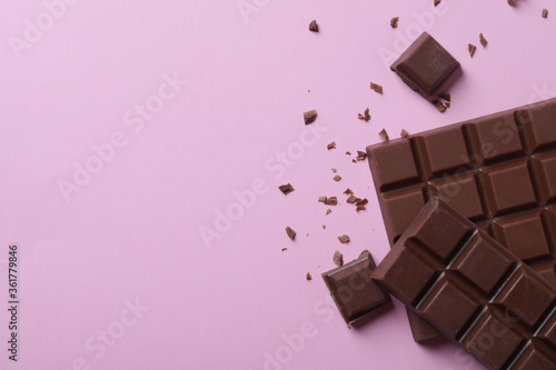 Fototapeta Tasty milk chocolate on pink background, flat lay. Space for text obraz