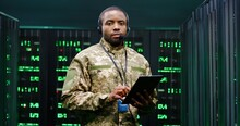 Portrait Of Young African American Handsome Army Technician In Uniform And Headset Holding Tablet Device And Turning To Camera In Server Room. Male Military Man Working In Data Analytic Center.