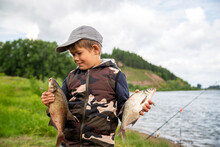 Seven Year Old Boy Holds A Fish He Caught