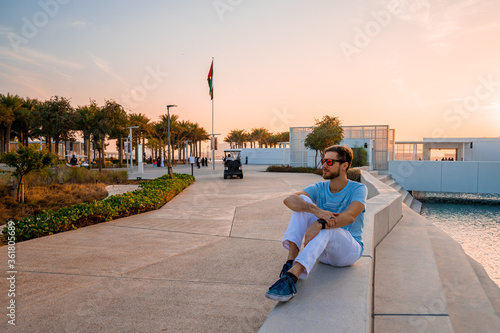 Fotografie, Obraz Young man sitting by the louvre in Abu Dhabi