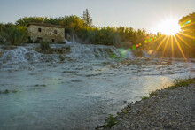 Rays Of The Rising Sun Over The Thermal Waters Of The Wild River In Saturnia In Tuscany, Italy
