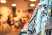 Closeup Shot Of Artist's Jeans Jacket Covered With Paint Hanging In A Studio On A Blurred Background
