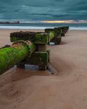Disused Wast Pipe On Blyth Beach, Northumberland, England, UK. On Overcast Morning At Dawn, With Incoming Waves.