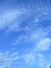 Vertical Shot Of The Blue Sky With White Clouds