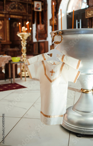 The christening shirt is hanging on a hanger on the bathhouse in the Church Fototapet