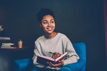 Positive African American Hipster Girl Looking Away Pondering On Planning To Do List In Textbook During Leisure At Home Interior, Smiling Dark Skinned Woman Writing Publication In Notepad