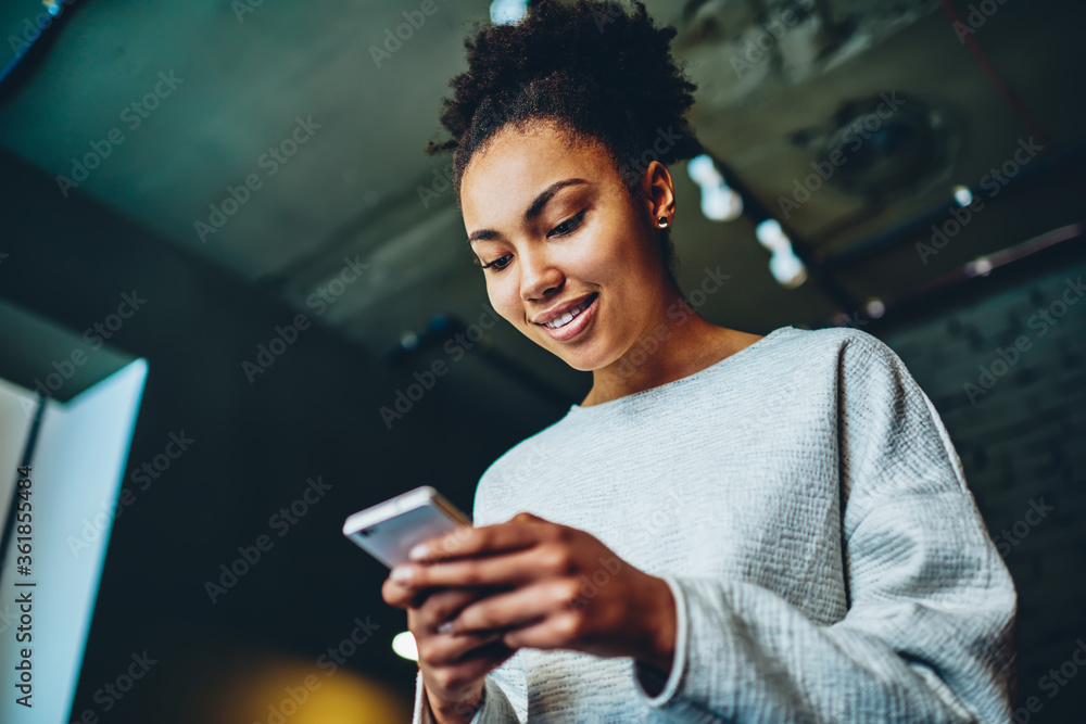 Fototapeta Cheerful african american girl checking mail in social networks using smartphone and wifi connection, positive dark skinned hipster guy share multimedia in personal blog enjoying app on cellphone