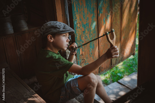 Canvas-taulu young boy with slingshot shooting