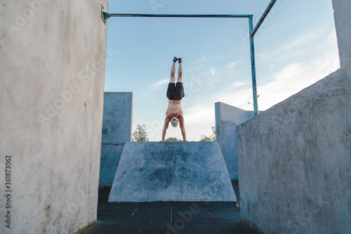 Obraz na plátně Handstand yoga pose by athlete man on the sport ground outdoors, natural lifestyle photo