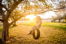 Young Caucasion Boy Playing On Backyard Tire Swing In Vibrant Afternoon Sunlight