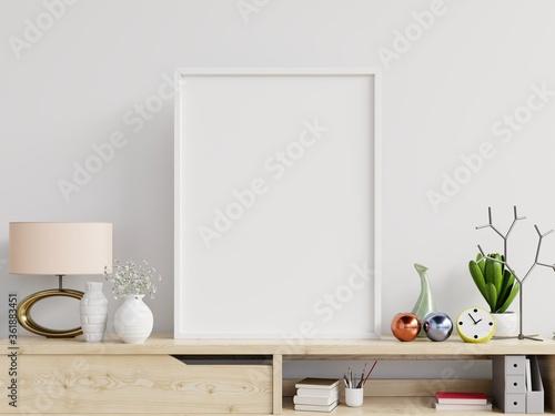 Fototapeta Poster mockup with vertical frame on table and white wall background. obraz na płótnie