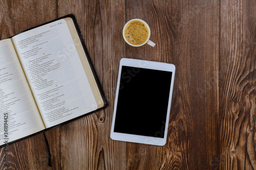 Fototapeta Open Holy Bible lying on wooden table in a reading the digital tablet with cup o