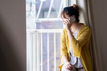 窓から外を眺めて電話をする女性