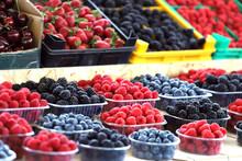 Raspberries, Blueberries And Blackberries On A Market In Plastic Bowls. Fruits Pattern.