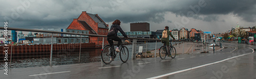 Fototapeta Panoramic crop of people cycling on urban street near canal with cloudy sky at background in Copenhagen, Denmark obraz