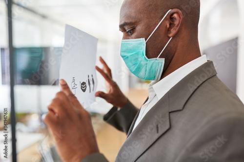 Geschäftsmann befestigt Aushang mit Hygieneregeln im Büro Canvas Print