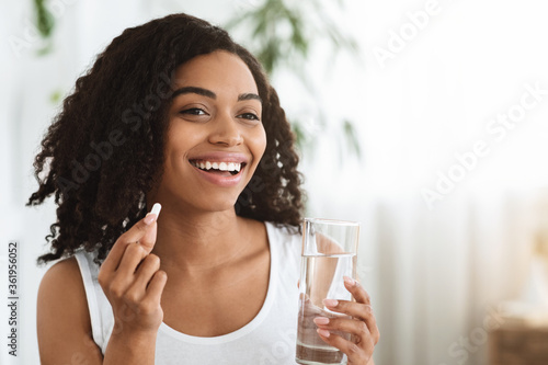 Healthy Diet Nutrition. Smiling Afro Woman Holding Vitamin Pill And Mineral Water
