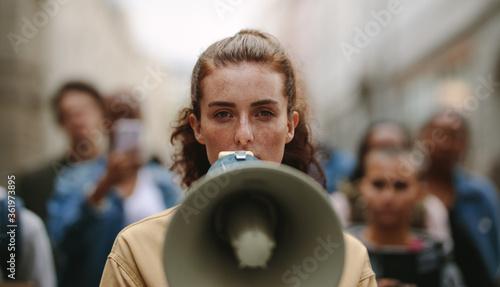 Obraz na plátně Female activist protesting with megaphone during a strike