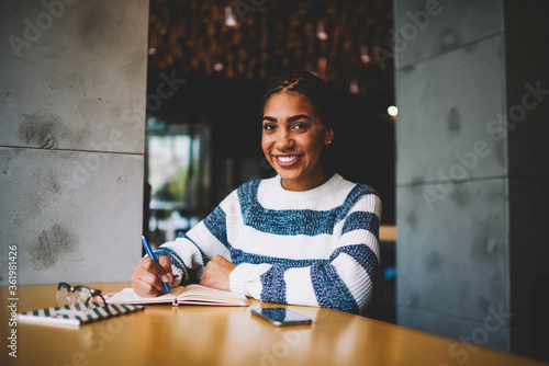 Tablou Canvas Half length portrait of successful afro american student smiling at camera while preparing homework task in cafe making research for coursework