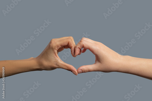Close-up of light-skinned and dark-skinned hands shaping in heart