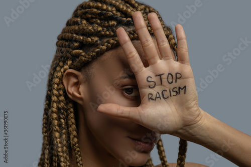 Young African American woman covering her one eye with palm with stop racism lettering