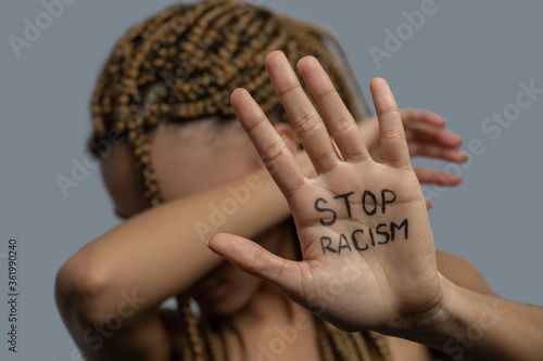 Young African American woman showing palm with stop racism lettering, covering her face with elbow