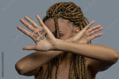 Young African American woman hiding her face behind crossed palms with stop racism lettering
