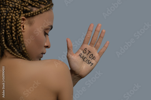 Young African American woman standing back to camera, showing palm with stop racism lettering above her shoulder