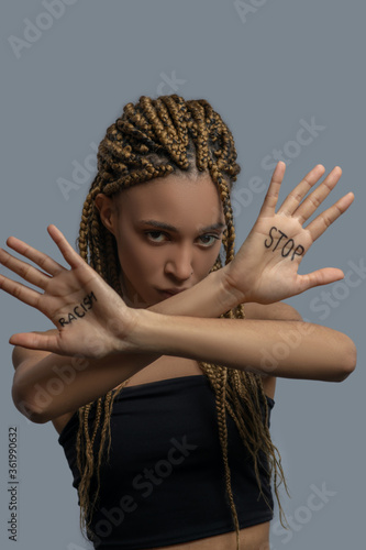 Sad young African American woman making cross with arms, showing palm with stop racism lettering