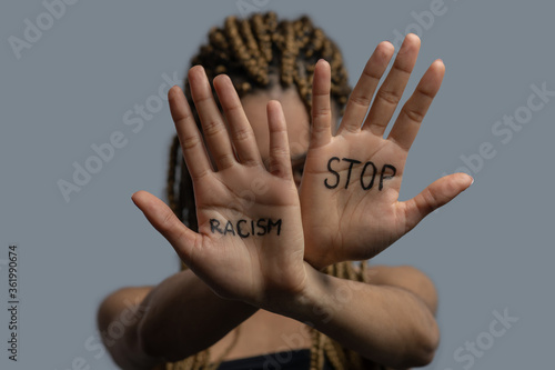 Young African American woman hiding her face with crossed palms, showing stop racism lettering