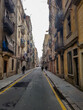 Barcelona small street road alley walk balconys flags old town Barcelonetta city center historic house buildings spain