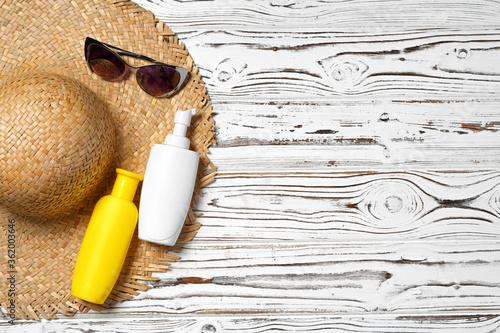 Fototapeta Straw hat, sunglasses and sunscreen bottle on wooden background obraz