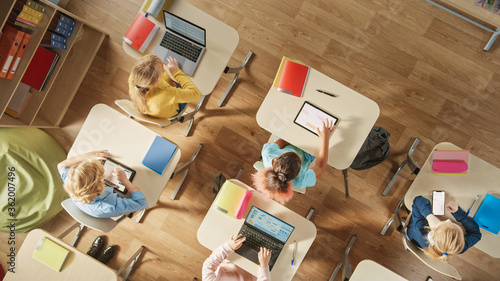 Top View Shot in Elementary School Computer Science Classroom: Children Sitting at their School Desk Using Personal Computers and Digital Tablets for Assignments Canvas Print