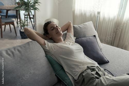 Fototapeta Happy woman lying on the sofa at home and relaxing obraz na płótnie