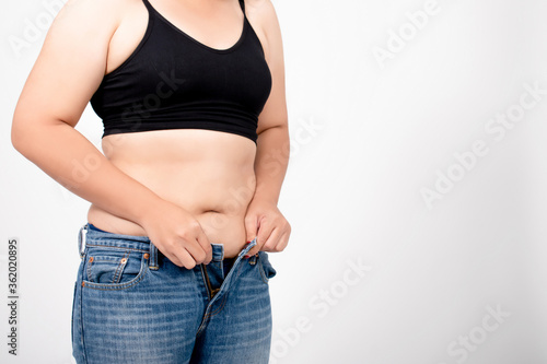 Obraz na plátně Asian women are overweight and have too much belly fat wearing jeans