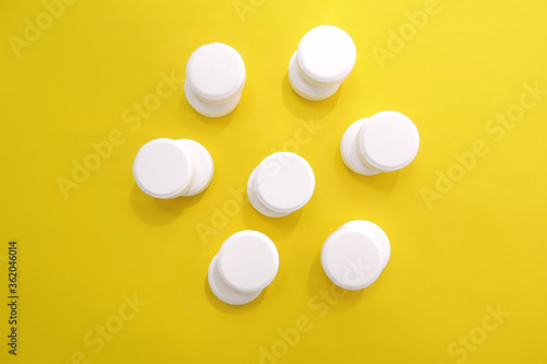 Photo white tablets of ascorbic vitamins laid out in the shape of a flower on a yellow